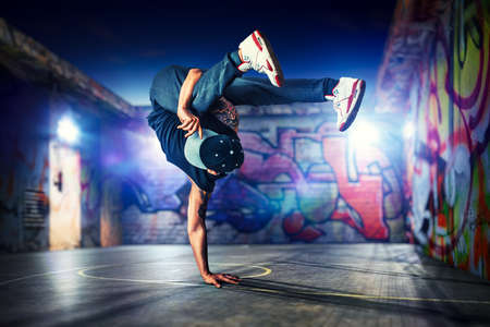Young man break dancing at night on urban painted walls background