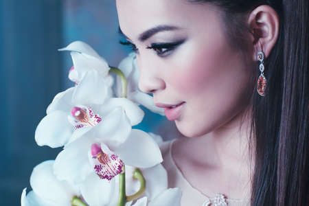 Young asian woman with orchid flower portrait close-up. Focus on lips. photo