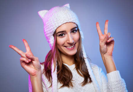 Young happy smiling woman showing victory sign. Warm winter white clothing. Stock Photo