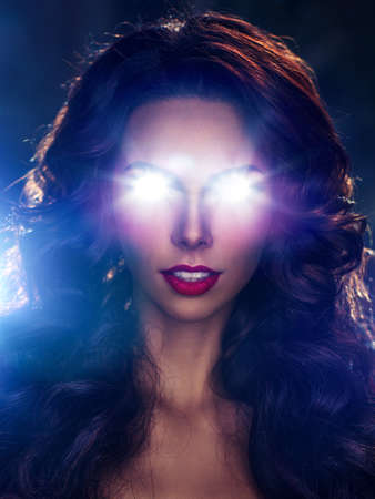 Sexy brunette woman with shining light from eyes portrait. Horror and power concept. photo