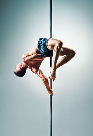 Young strong pole dancing man on wall background