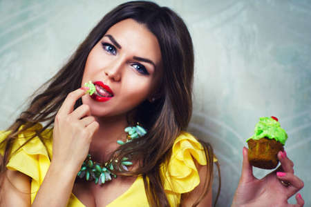 Young sexy brunette woman eating high-calorie cake photo