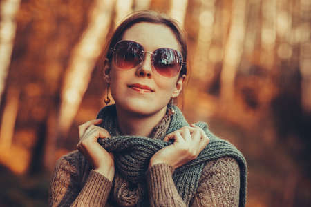 autumn colors: Young woman with sunglasses autumn portrait. Red film style retro colors effect.