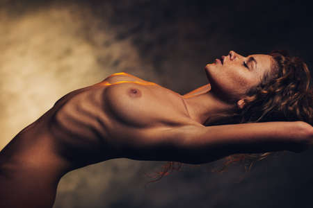 Young sensual naked woman resting in air concept. Soft vintage film style colors effect. Stock Photo