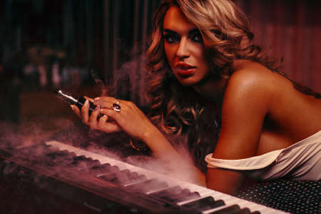 Young woman musician sensual fashion portrait. Smoking and playing piano in dark night interior. photo