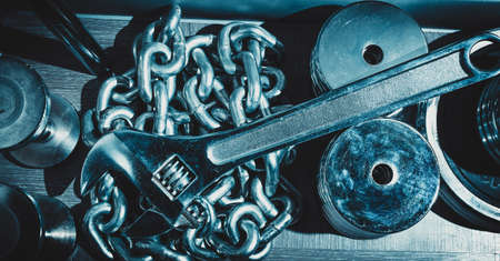 adjustable dumbbell: Metallic background with heavy chain and adjustable wrench and dumbbell. Blue tinting. Stock Photo