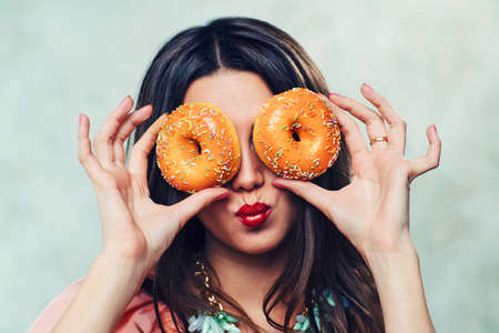 Young sexy brunette woman with donuts portrait photo