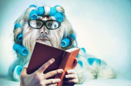 Clever long hair dog with mans face in glasses reading book. Mutation and genetic modification  fun concept. Stock Photo