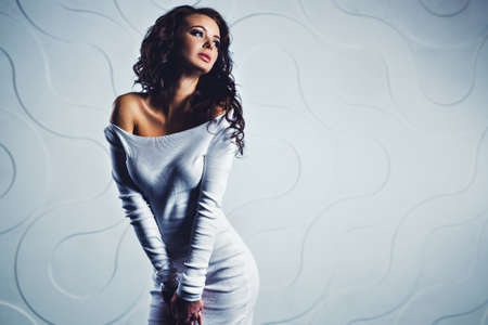 Young slim sexy brunette woman in white dress portrait in modern interior photo