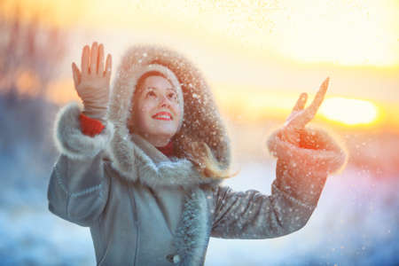 warm clothing: Young happy woman in warm winter clothing throwing up snow. Red sunset colors. Stock Photo