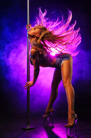 Young slim woman pole dancing in dark club interior with lights and smoke