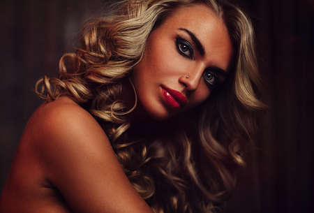 Young woman sensual fashion portrait with makeup and long blond hair in dark interior photo