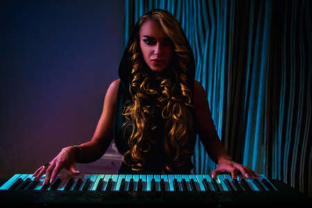 Young woman musician sensual fashion portrait. Playing piano in dark night interior. photo