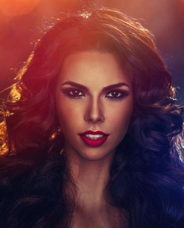 Young sexy brunette woman with long lush curls fashion portrait. Blue and red lights shine effect. photo