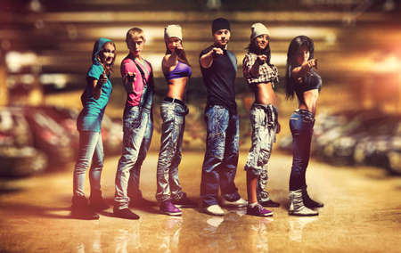Six people modern dancers team. Showing pointing hand sign. Underground car parking interior. photo