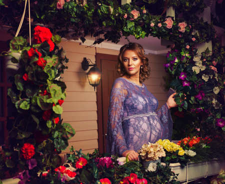 Young pregnant woman tender portrait at house with lots of flowers photo