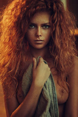 Young woman with red hair indoors nude portrait Archivio Fotografico