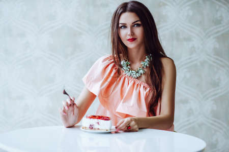 Young sexy brunette woman sitting at table and eating high-calorie cake