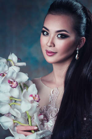 Young asian woman with orchid flower portrait photo