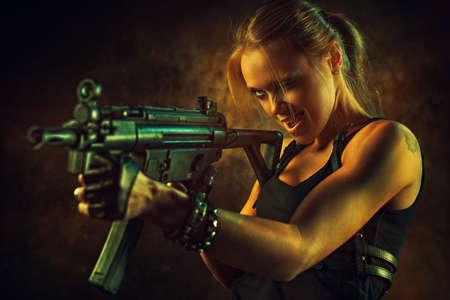 pistola: mujer fuerte joven con el arma grande en el interior urbano dramático. Tatuaje en el cuerpo.