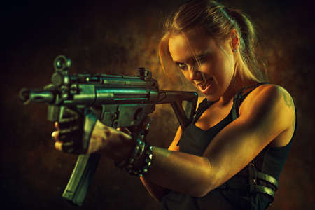 women with guns: Young strong woman with big gun in dramatic urban interior. Tattoo on body.