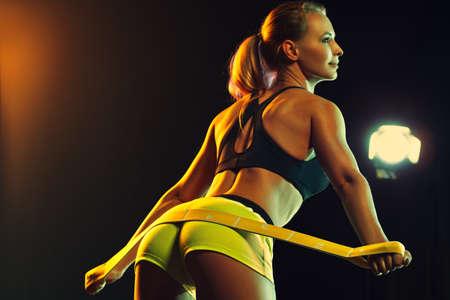 Jonge sexy sportieve vrouw die oefeningen voor haar buit fit. Focus op buit.
