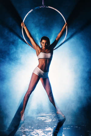 Young slim sports woman in white clothing with ring. Smoke and blue light from back. photo