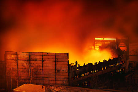 Big fire in store at night. Building is burned and collapsed. Stock Photo