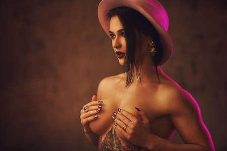 fille sexy nue: Jeune femme brune brune sexy en portrait de chapeau. Avec tatouage sur le corps et les piercings sur le visage.