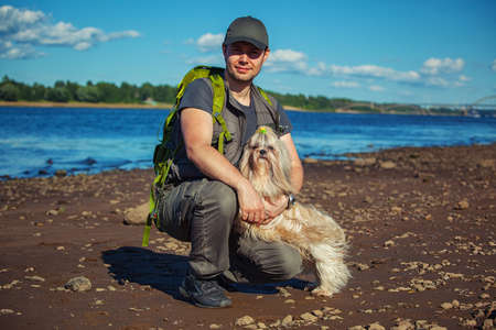 Young man tourist with shih-tzu dog on river shore