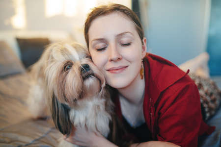 Young woman with shih tzu dog portrait. Love and care to pet concept. Stock Photo