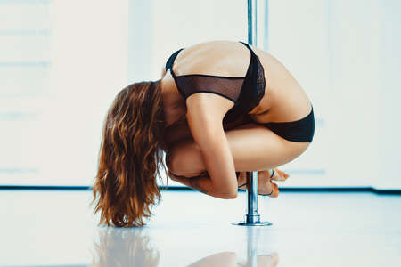 Young slim pole dance woman in black lingerie hanging on pole above floor. Tattoo on hand.