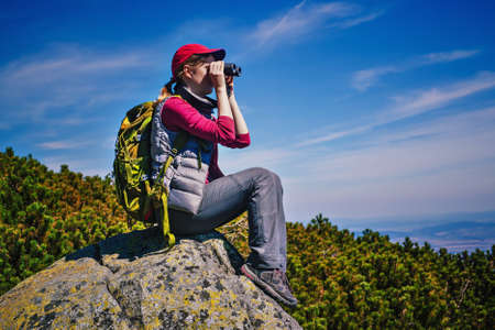 far away look: Young woman tourist with green backpack sitting on mountain top and looking in binoculars