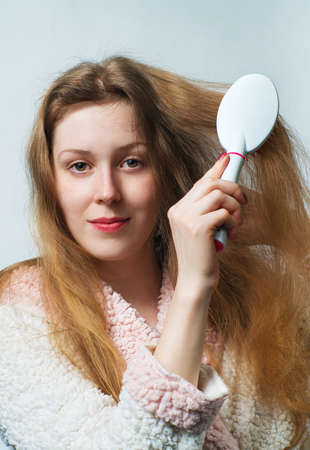 Young blond woman in bathrobe comb hair after washing. On white background. photo