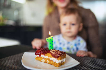 One year baby celebrating birthday. Focus on cake with candle. photo