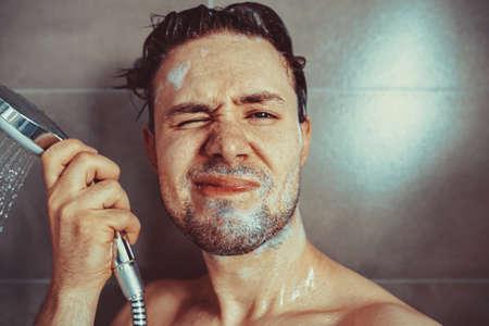 Jonge man wassen hoofd met shampoo in badkamer portret. Ongelukkige emoties.