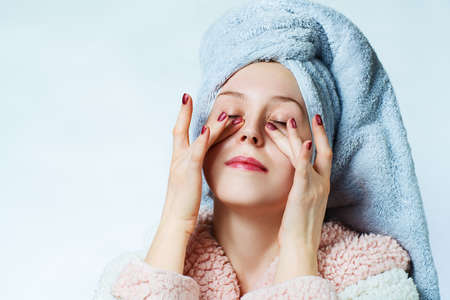 Young woman with bathrobe and towel doing massage under eyes. Beauty spa portrait. photo