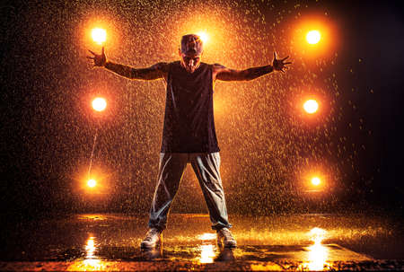 Young man break dancer standing in club with lights and water. Tattoo on body.