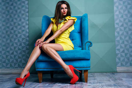 Young woman in yellow dress in modern interior on blue chair photo