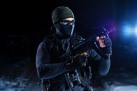 Strong man military special forces standing with gun on snow at night photo