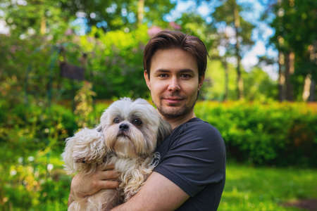 Young man with shih tzu dog portrait in summer garden. Love and care concept. photo