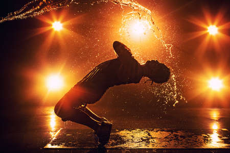 Young man break dancer with lights and water effects. Tattoo on hand.