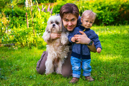 Father with son and dog together portrait in summer green garden photo