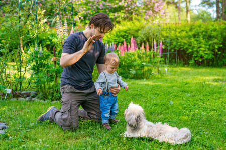 Father teaching son how to command the dog in summer green garden photo