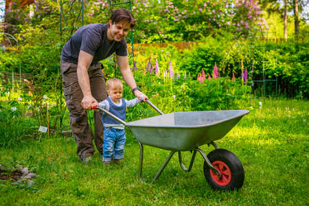 Father with son working in summer garden and holding wheelbarrow photo