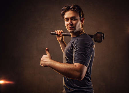 Young strong man with hammer on wall background photo