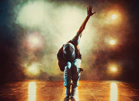 Jonge man breekt dansen in club met lichten en rook. Tattoo op het lichaam. Stockfoto