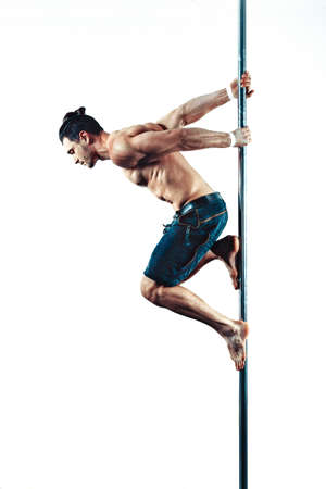 Young strong pole dancing man on white wall background Stock Photo