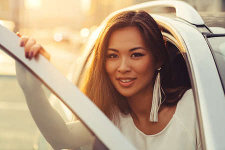 Young asian woman opening car door portrait on city background. Warm sunset light. Stock Photo