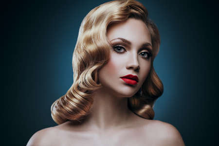 Young elegant blond woman fashion portrait. Curly hair and red lips makeup.